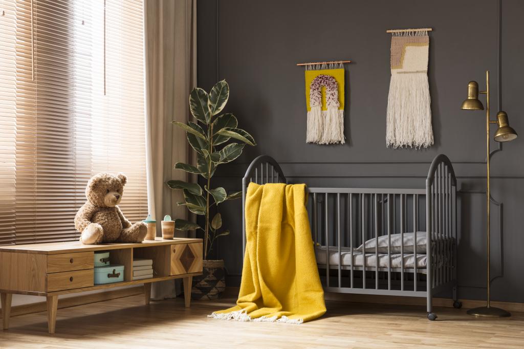 Chambre d'enfant murs foncés sol en parquet et couverture jaune