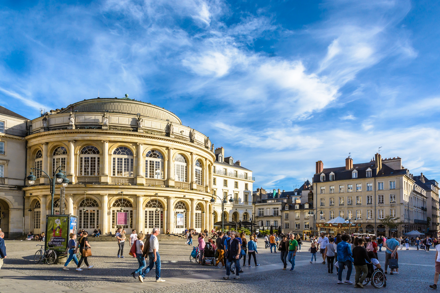 Rennes, France – October 13, 2018: People strolling on the pedestrian town hall square in front of the rounded facade of the opera house by a sunny saturday afternoon under a deep blue sky.