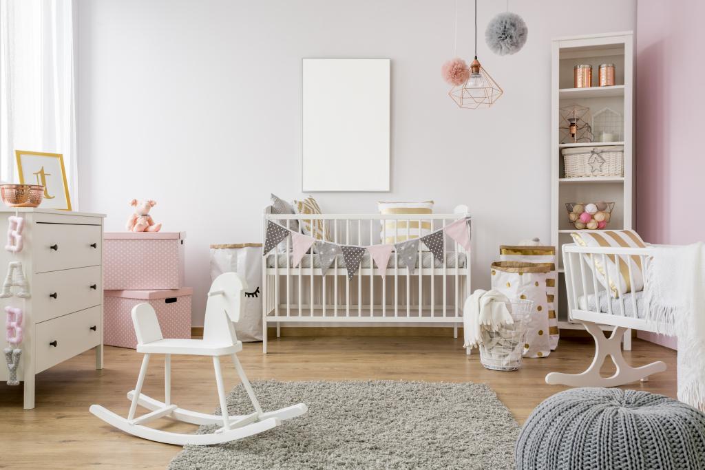 chambre de bébé décorée en rose avec cheval à bascule, tapis, commode et pouf