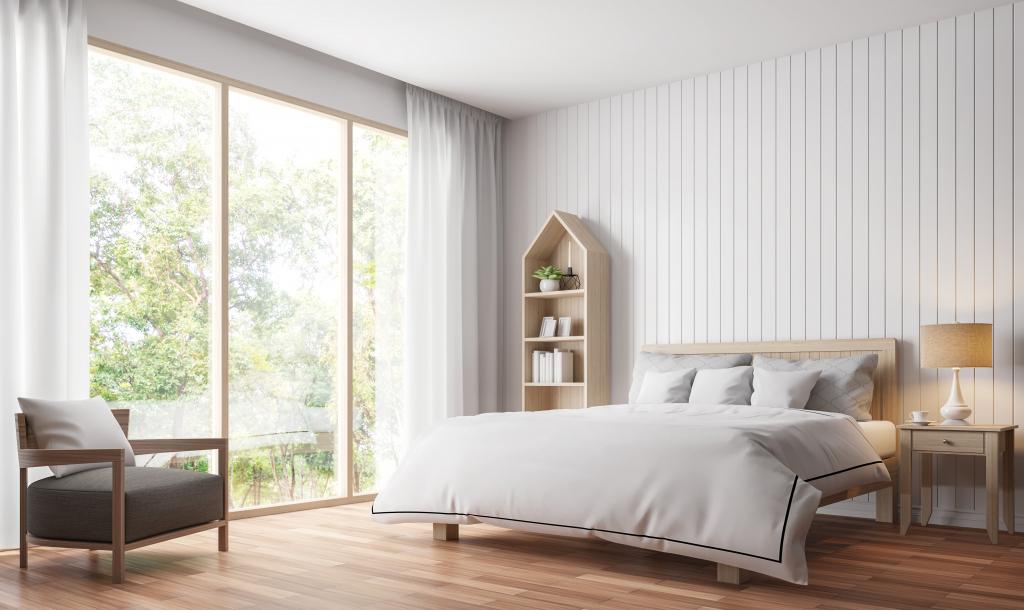 Gérer la luminosité dans une chambre en installant une grande baie vitrée.