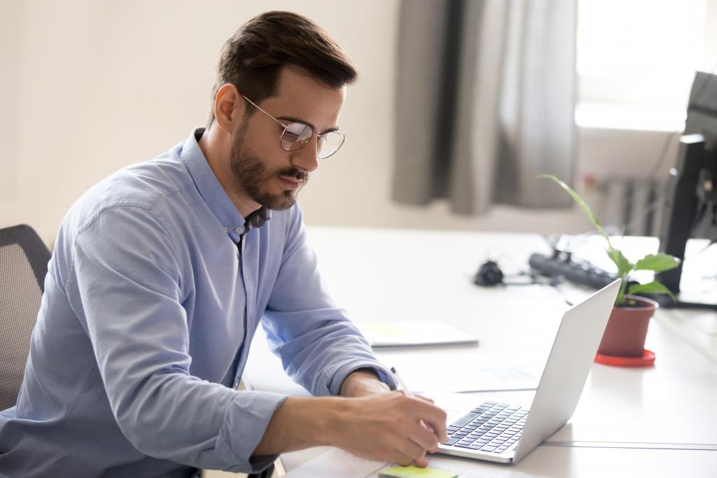 Homme prenant des notes devant un ordinateur portable