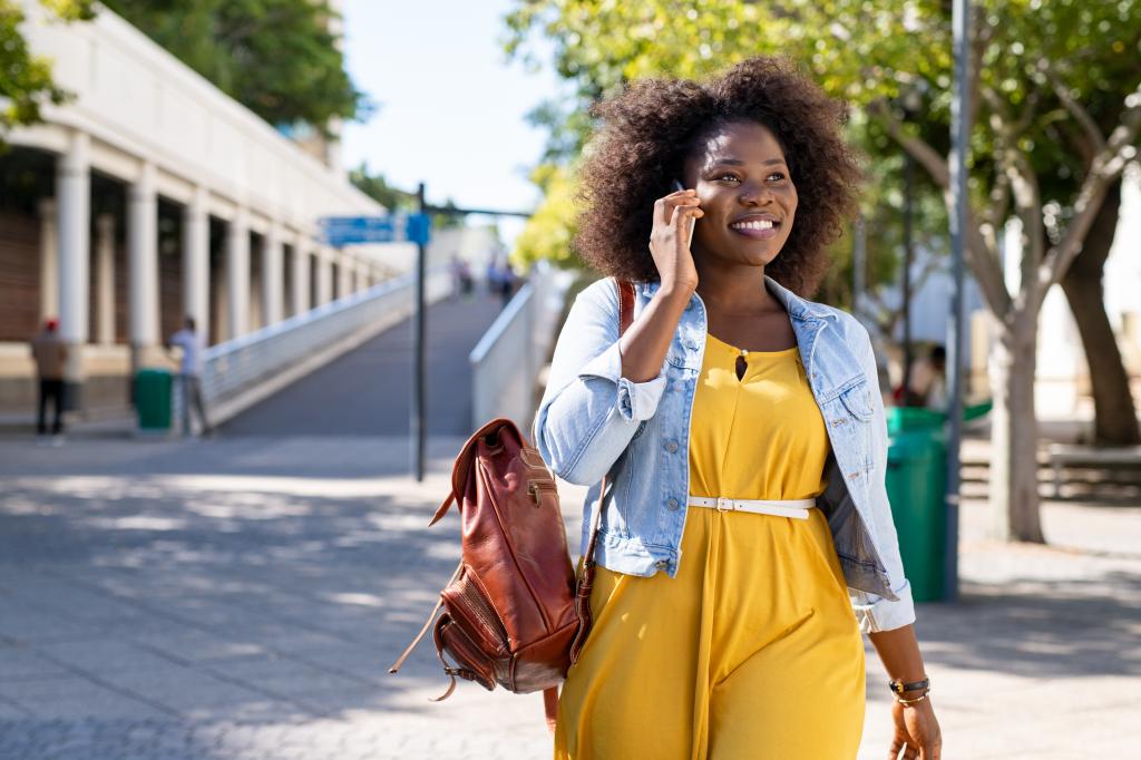 Femme qui marche dans la rue au téléphone avec le sourire