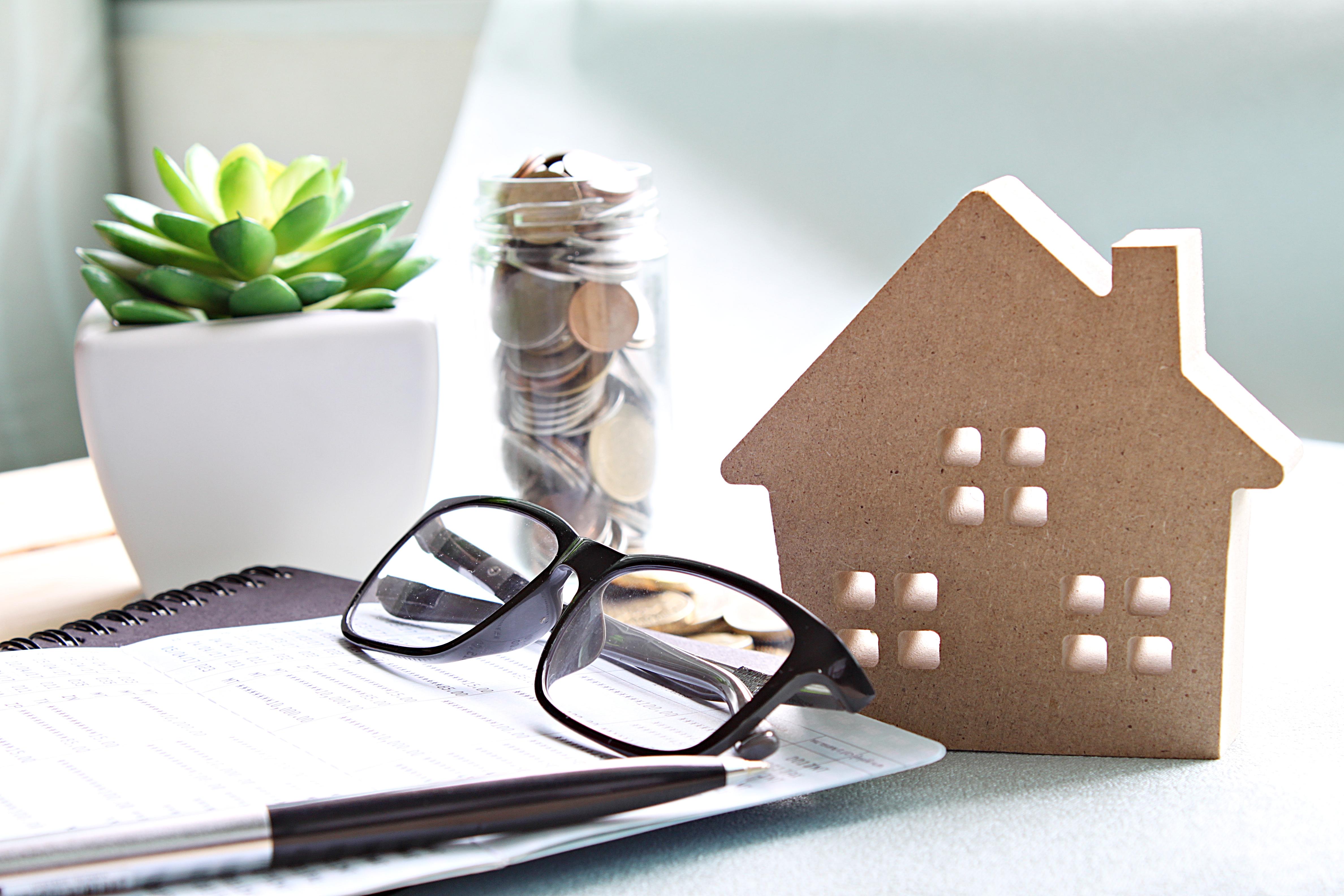 Maisonnette en bois, lunettes de vue, stylo et pièces de monnaies