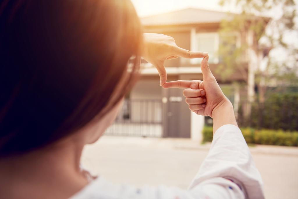 Mains qui forment un cadre pour faire semblant de prendre une photo de maison depuis la rue pendant une visite immobilière