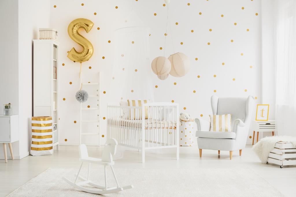 Décoration blanche avec des touches de doré dans la chambre de bébé