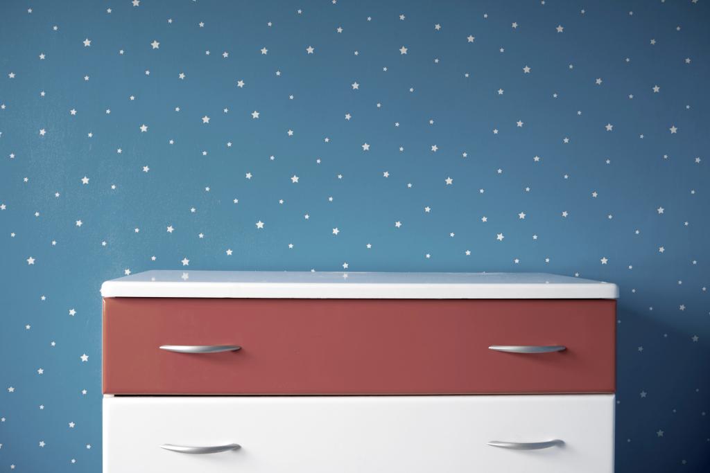 Mur avec papier peint étoilé et commode peinte.