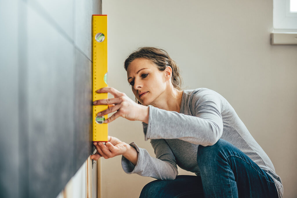Femme qui prend des mesures pour définir le coût des travaux