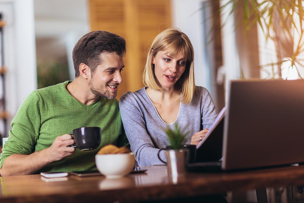 Couple devant un ordinateur préparant un dossier de souscription à un crédit immobilier