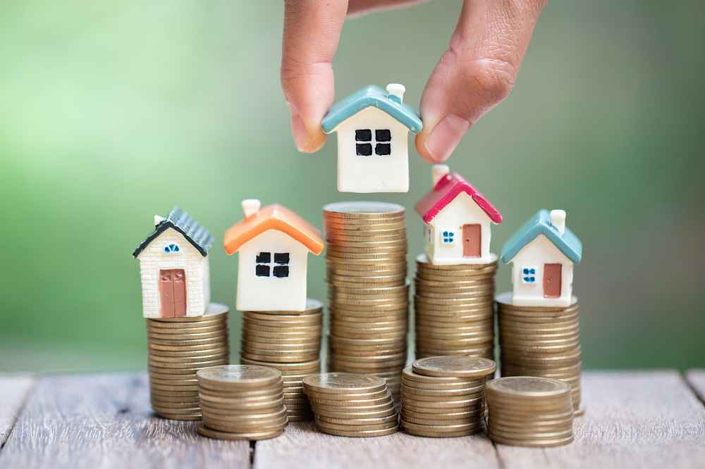 Estimation bien immobilier. Pièces de monnaie. Maisons miniatures