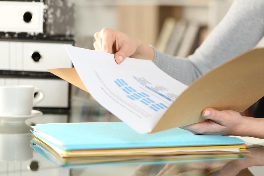Mains de femme vérifiant des documents dans un dossier de location