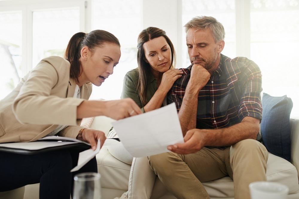 Couple signe le mandat de vente avec l'agent immobilier.