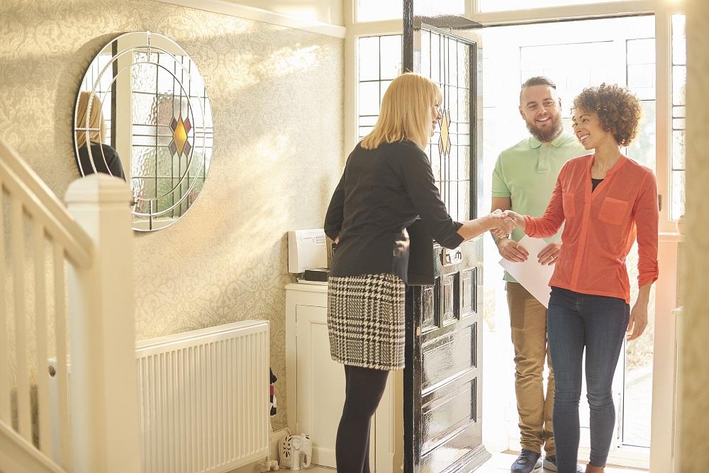 Jeune couple visite un bien immobilier avec un agent immobilier.