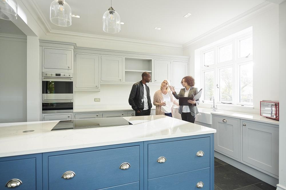 Couple en visite d'une maison avec un agent immobilier dans la cuisine