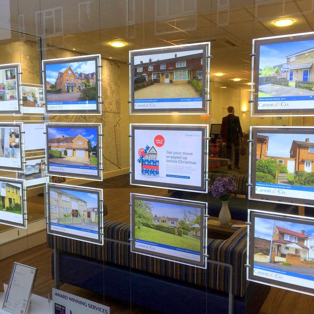 Vitrine d'agence immobilière avec biens à vendre