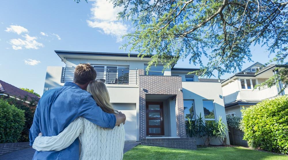 Jeune couple devant la maison de leurs rêves.