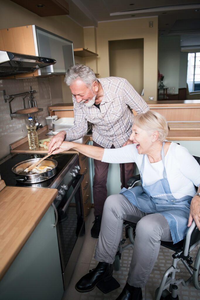 Une femme en fauteuil roulant cuisine en rigolant avec son mari dans une cuisine aménagée.