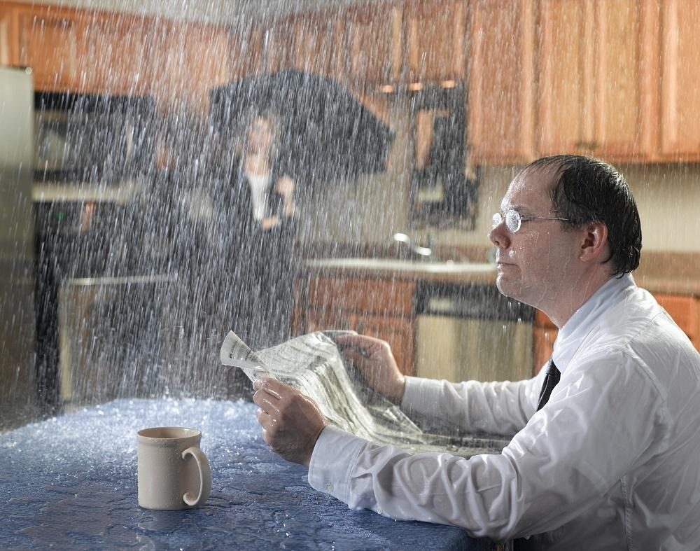 Homme lit son journal à table sous l'eau qui coule du plafond. Femme avec parapluie en arrière-plan.