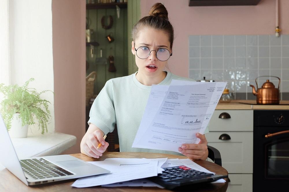 Jeune femme choquée avec les factures de ses charges locatives à la main