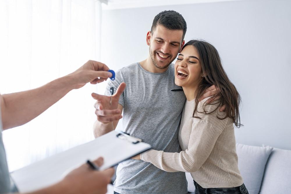 Jeune couple reçoit les clefs après l'état des lieux du logement en location