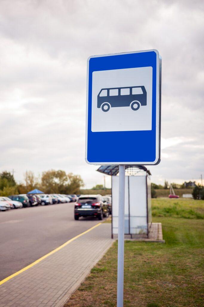 Panneau d'un arrêt de bus avec l'abri en arrière-plan