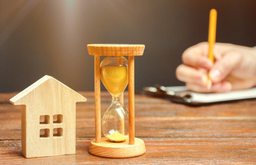 Symboles d'une maison et d'un sablier en bois et la main d'une personne signant des documents.