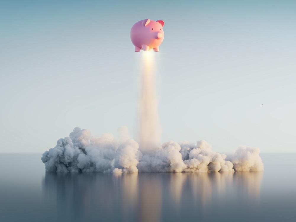 Tirelire cochon rose en train de décoller comme une fusée.