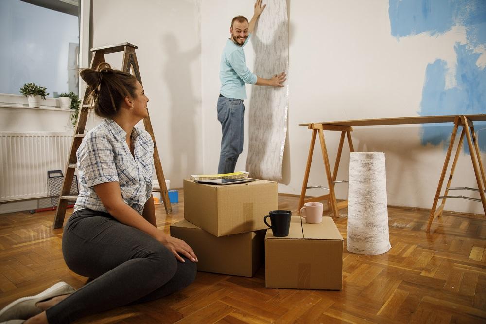 Jeune couple fait des travaux de peinture et de pose de papier peint.