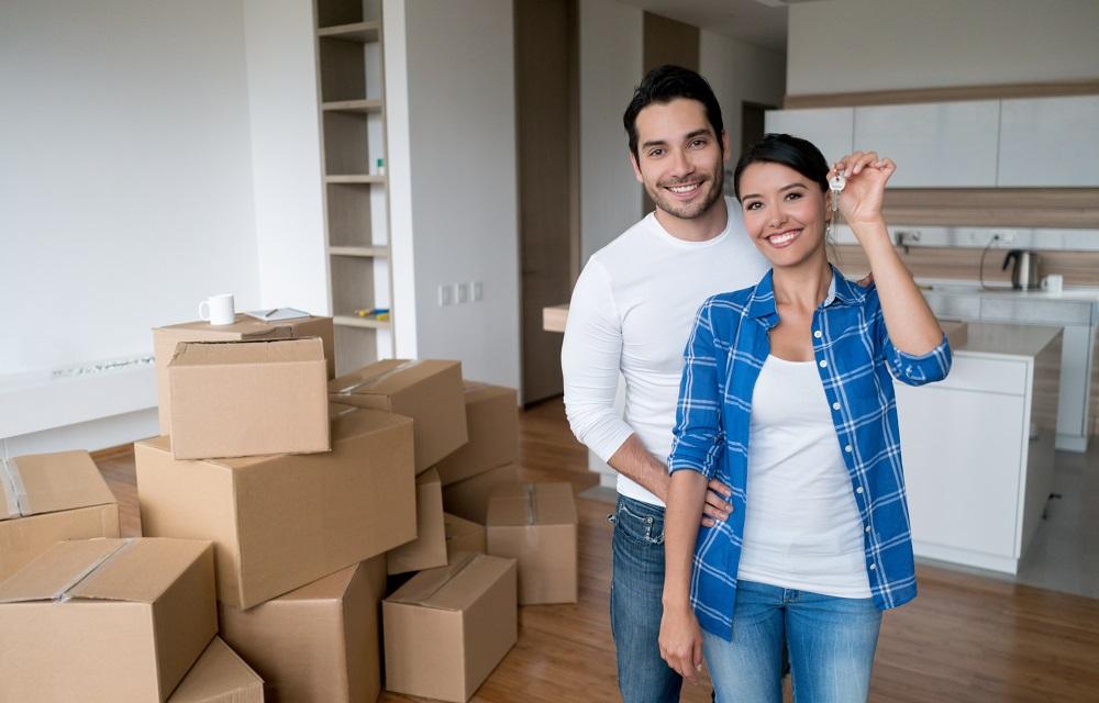 Jeune couple aménage dans son appartement en location et montre ses clefs.