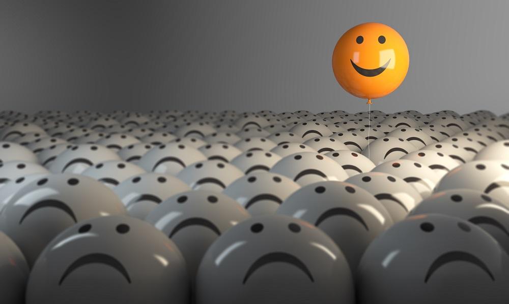 Un ballon jaune avec un sourire au dessus des ballons gris avec visages tristes