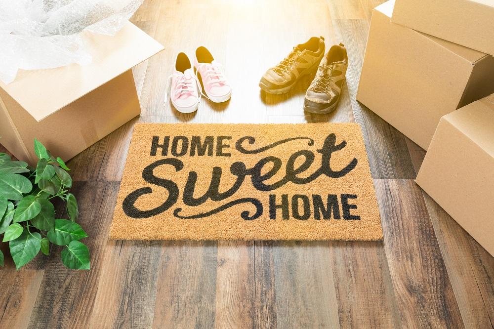"""Paillasson avec l'écriture """"Home sweet home"""" à côté des cartons de déménagement et deux paires de chaussures."""