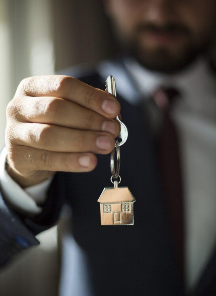 Agent immobilier tendant les clefs vers le nouveau propriétaire