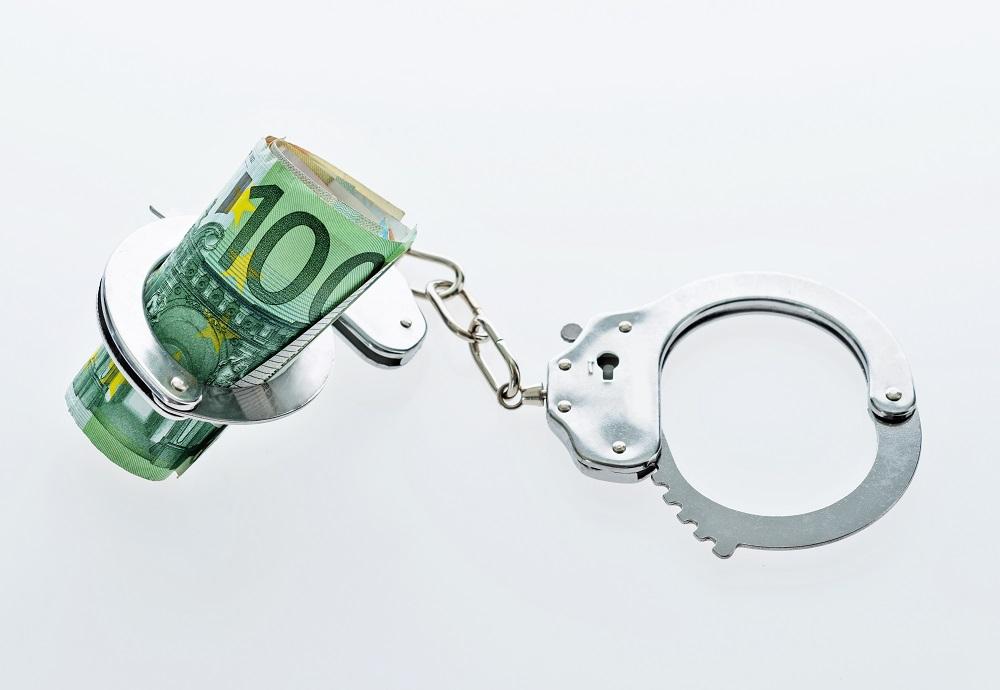 Menotte autour d'une liasse de billets symbolisant la caution bancaire