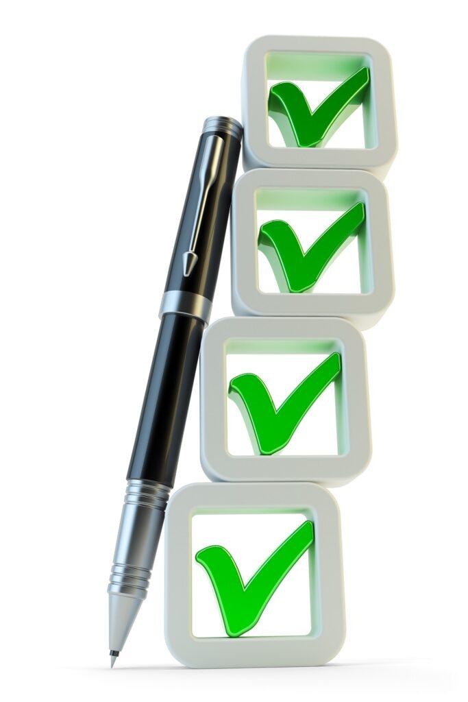 Un stylo noir à côté des cases à cocher empilées symbolisant un checklist de dossier de candidature